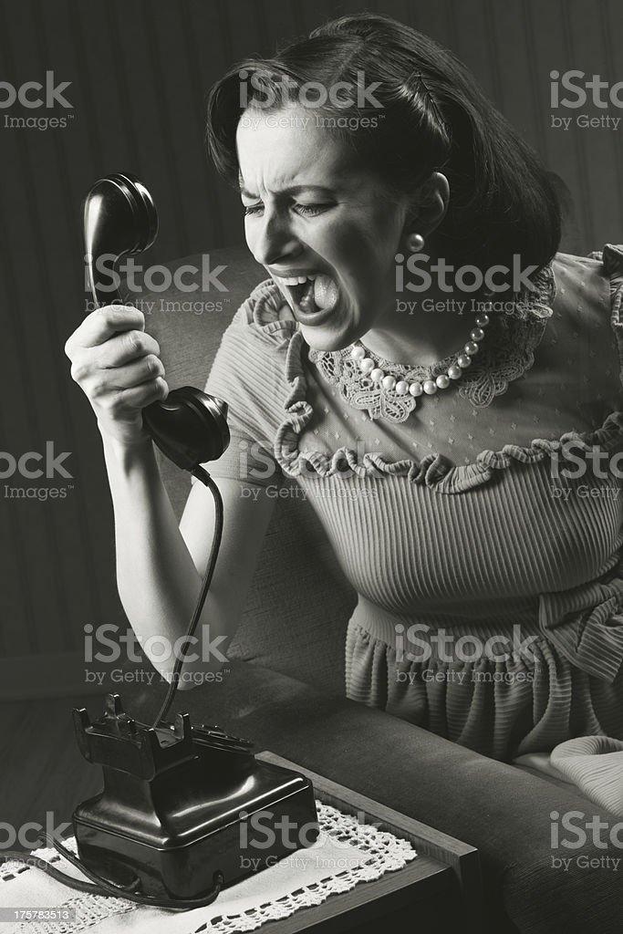 Angry woman screaming at retro phone, 1950 style royalty-free stock photo