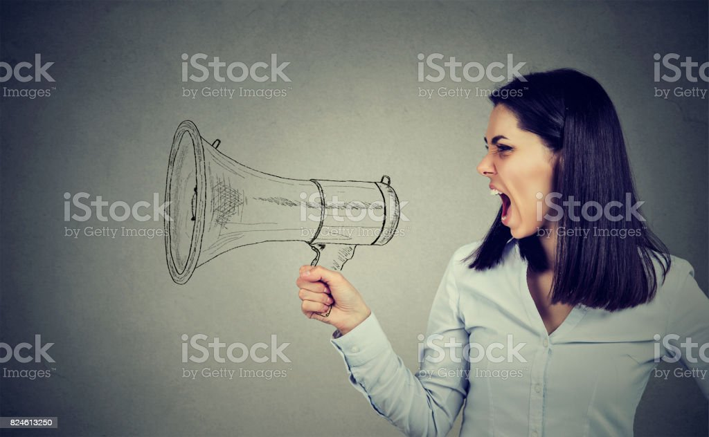angry woman screaming in megaphone stock photo