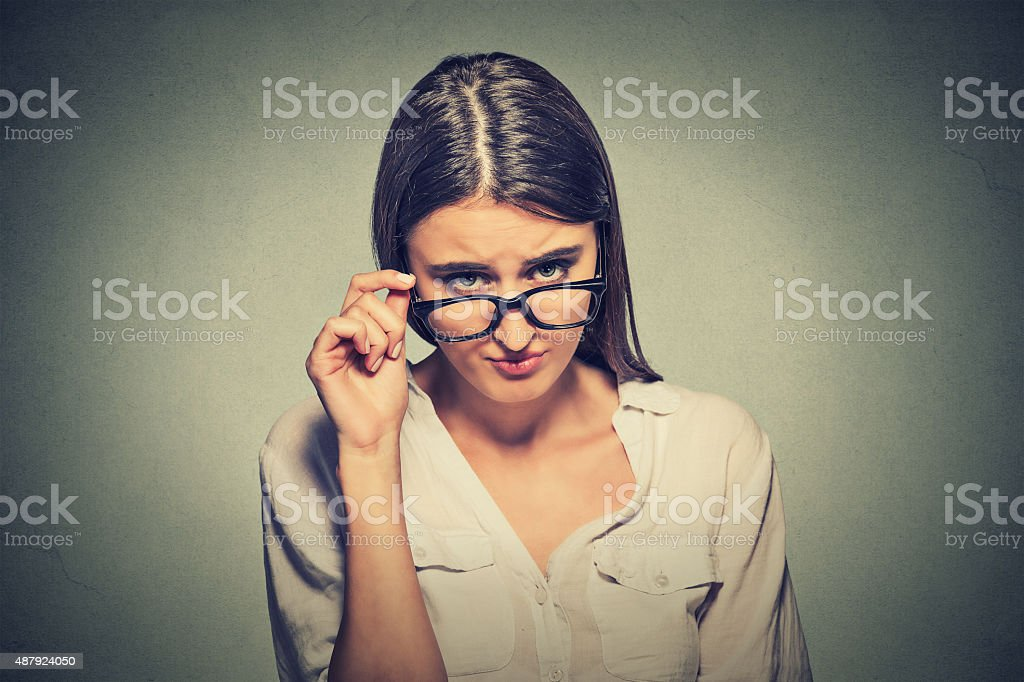 angry woman with glasses skeptically looking at you stock photo