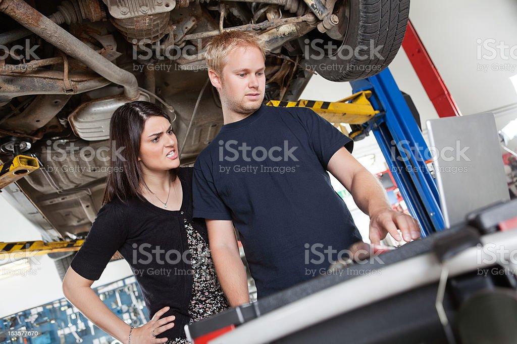 Angry woman with mechanic stock photo