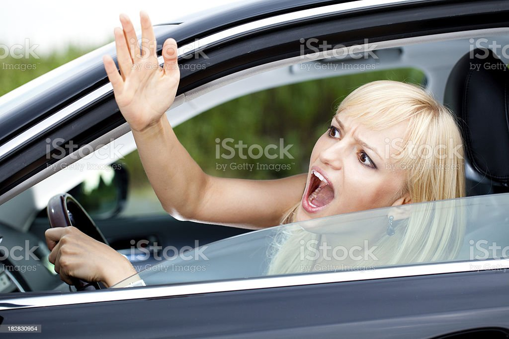 Angry woman with road rage driving a car stock photo