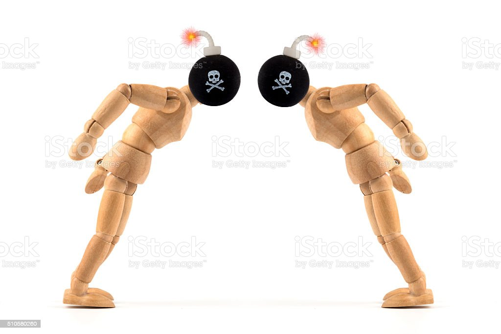 angry wooden mannequin fighting with bombs as head stock photo