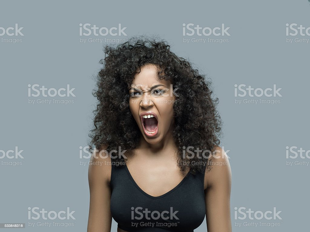 Angry young adult female screaming stock photo