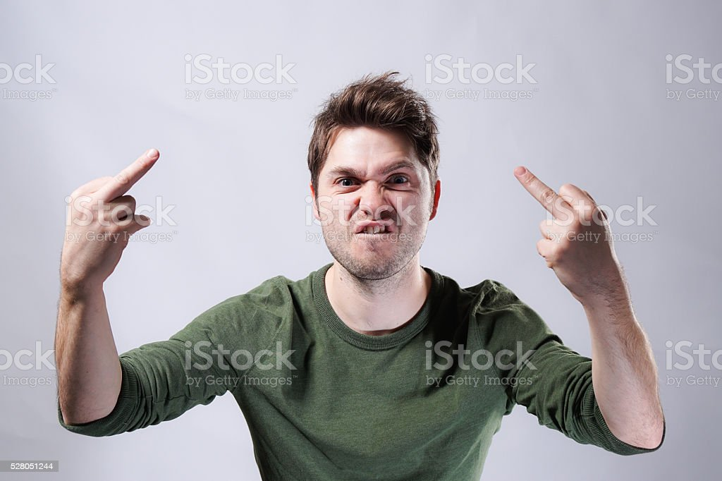 Angry young adult man flipping middle fingers on white background stock photo