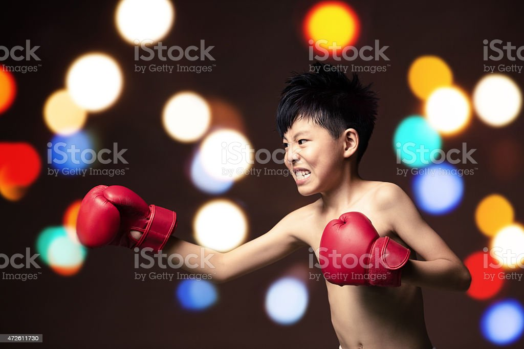 angry young boy play boxe with gloves stock photo