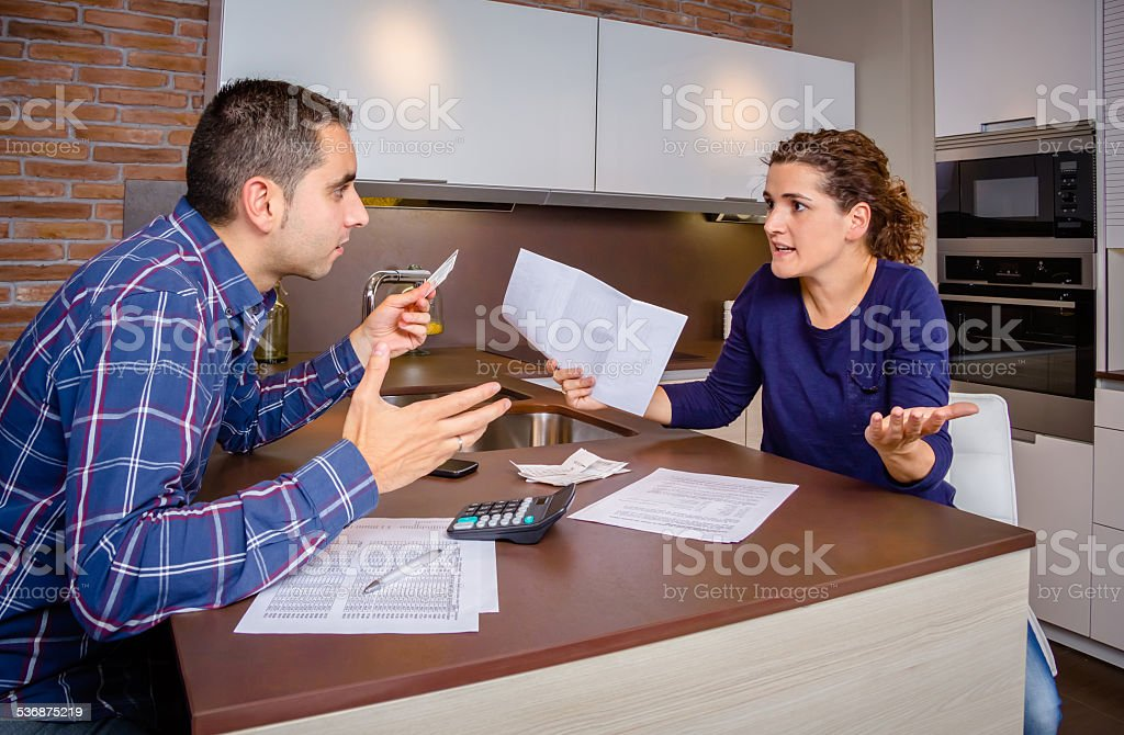 Angry young couple arguing by credit card debts stock photo