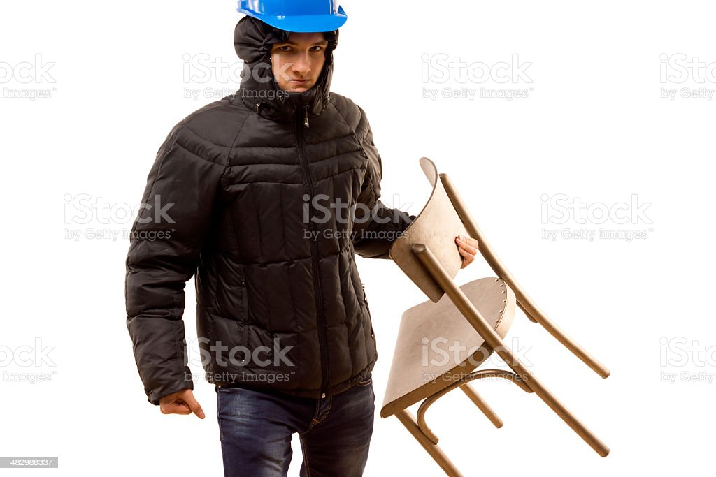 Angry young hooligan carrying a wooden chair stock photo