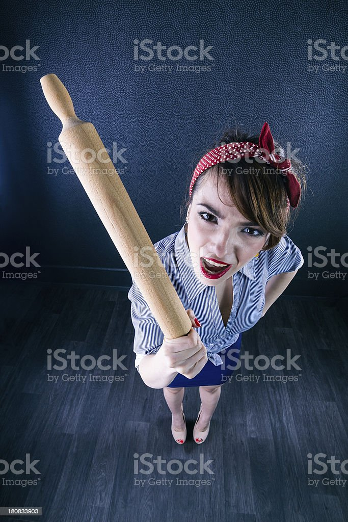 Angry young housewife holding rolling pin... royalty-free stock photo