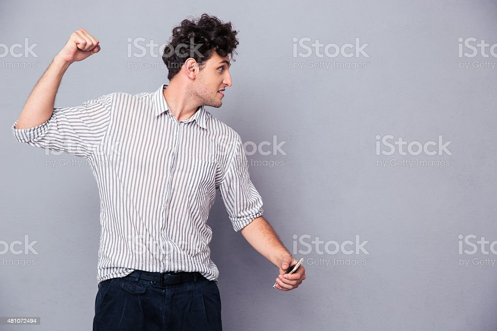 Angry young man clenching his fist stock photo
