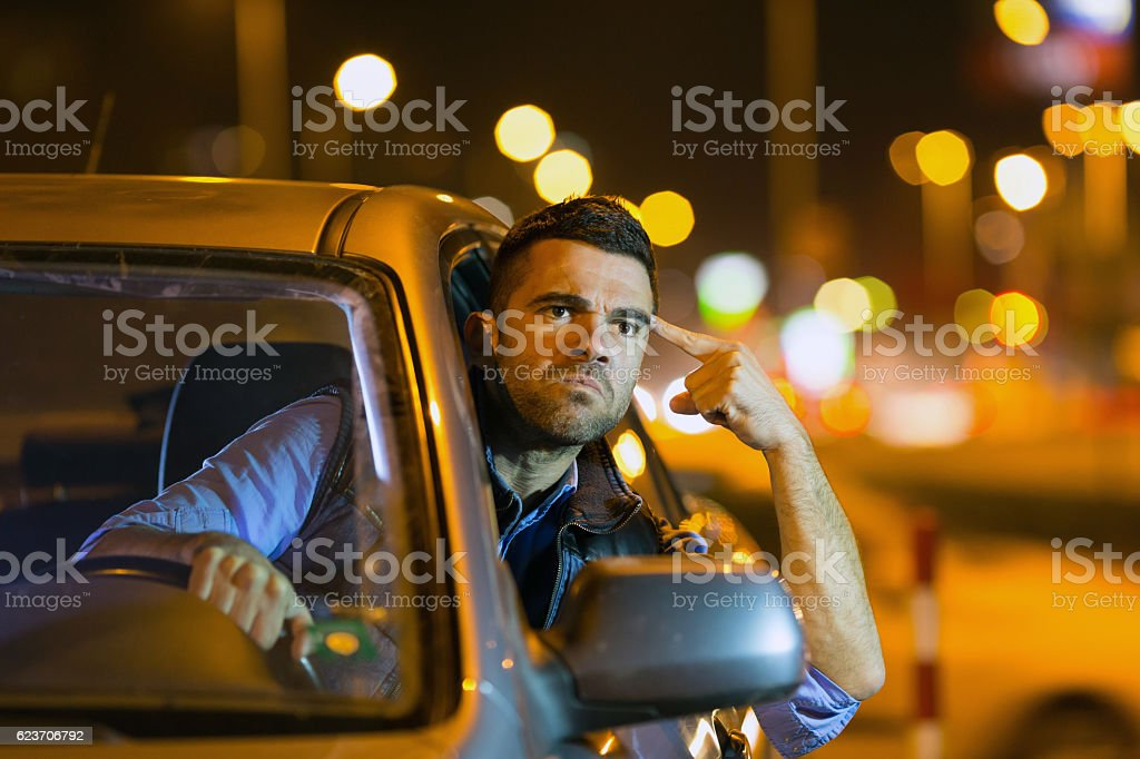 Angry young man driving car at night stock photo