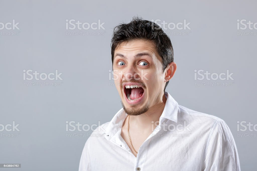 angry young man in the white shirt screaming on a grey backgroun stock photo