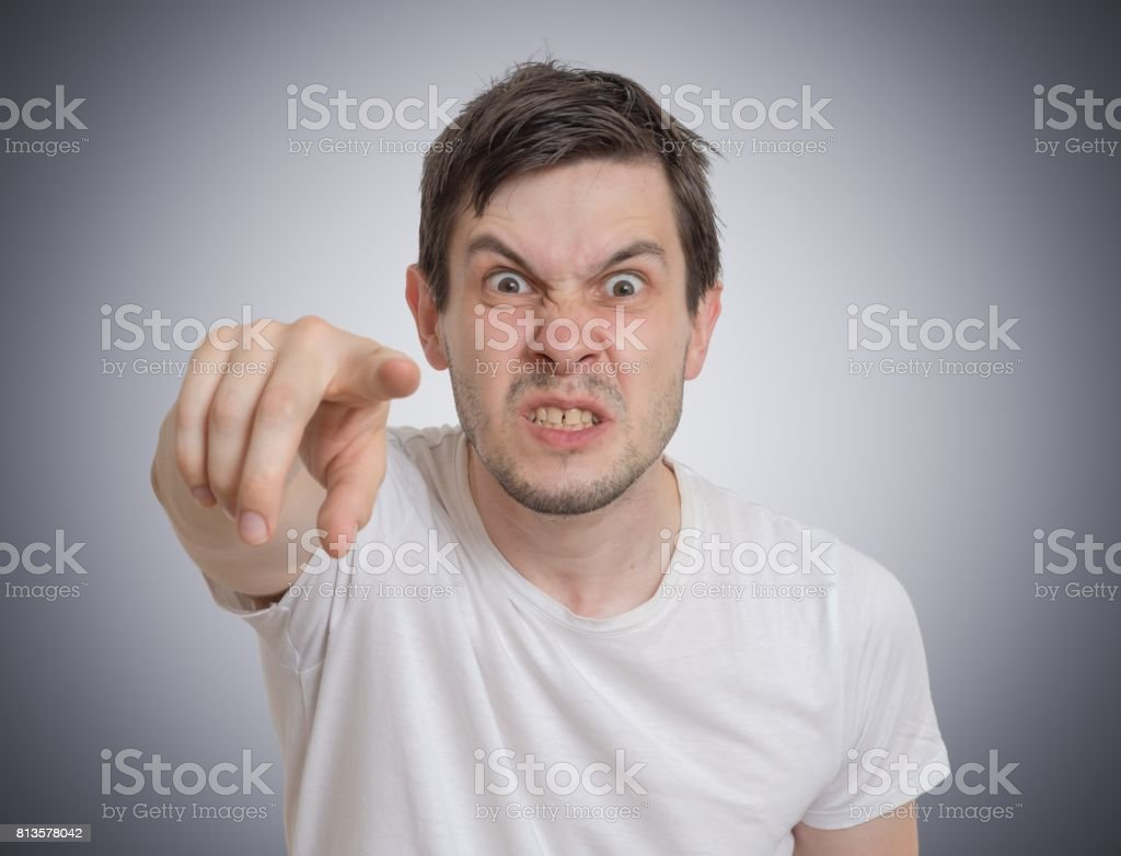 Angry young man is pointing towards you. stock photo