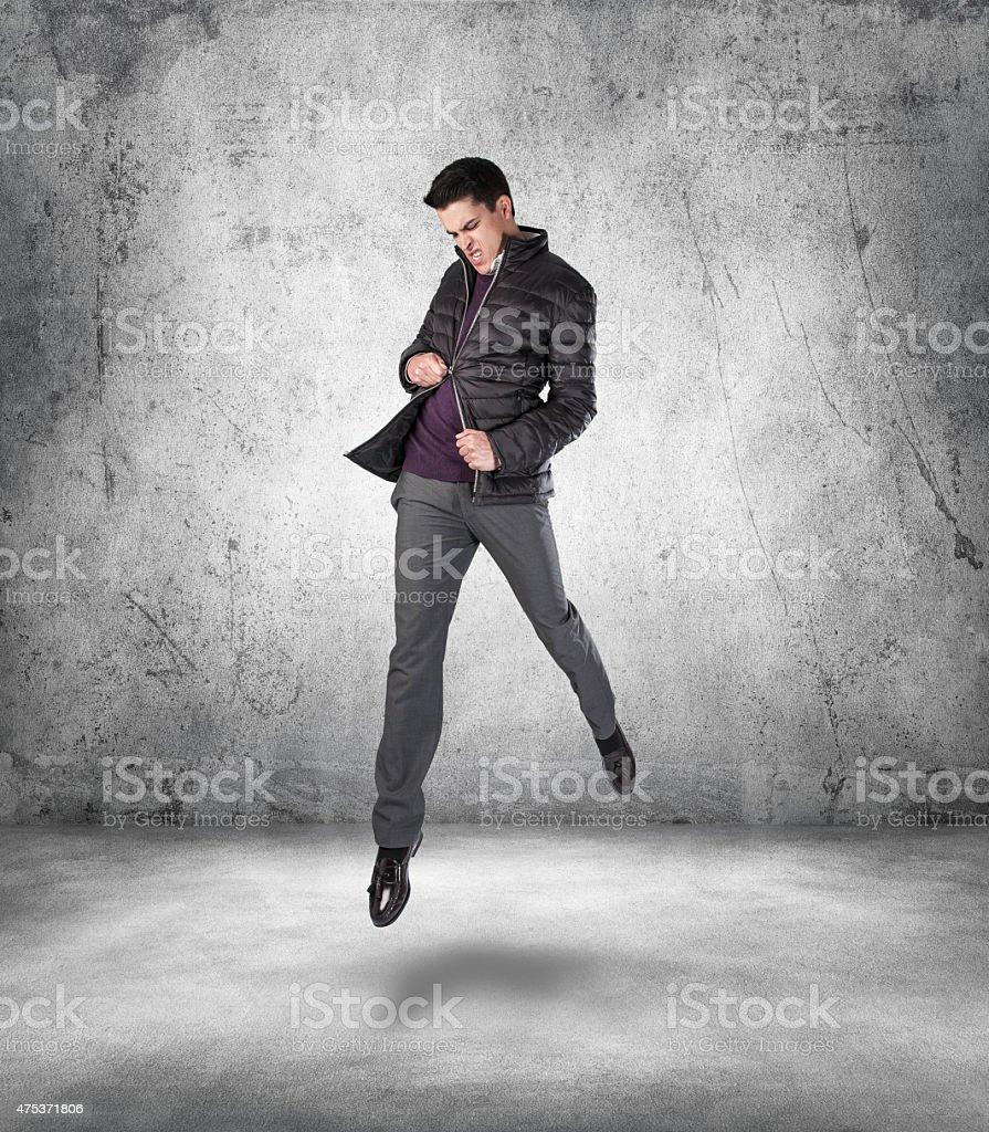 Angry Young Man Jumping and Pulling at his Broken Zipper stock photo
