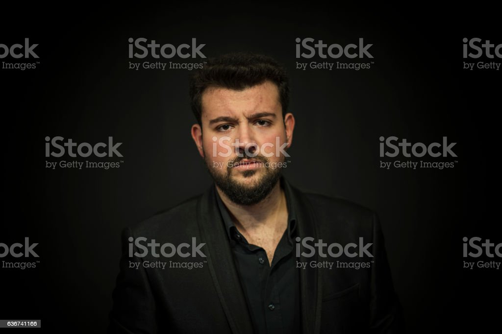 Angry Young Man Posing Front of a Black Wall stock photo