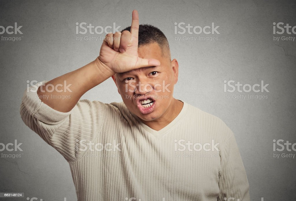angry young man showing loser sign on forehead, looking at you stock photo