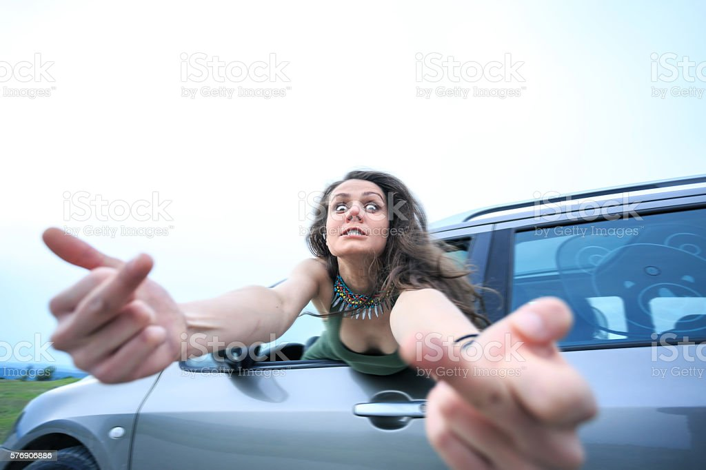 Angry young woman looking at camera and making abusive gesture stock photo