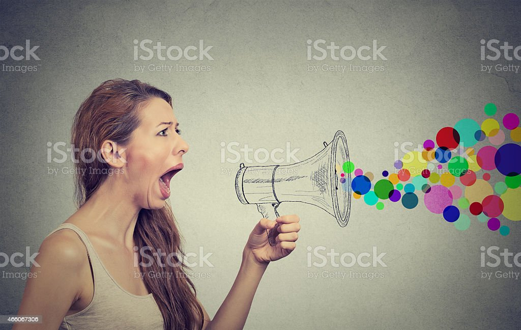 Angry young woman screaming in megaphone stock photo