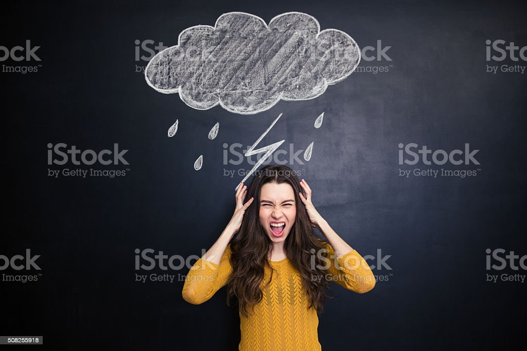 Angry young woman screaming over blackboard behind her stock photo