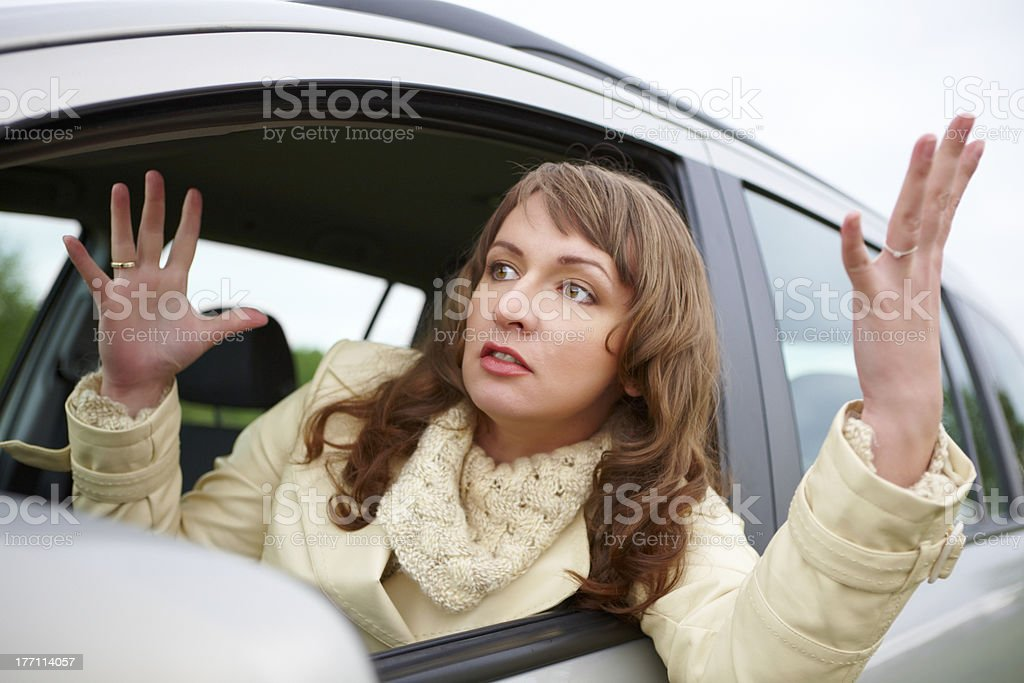 Angry young woman sitting in a car stock photo