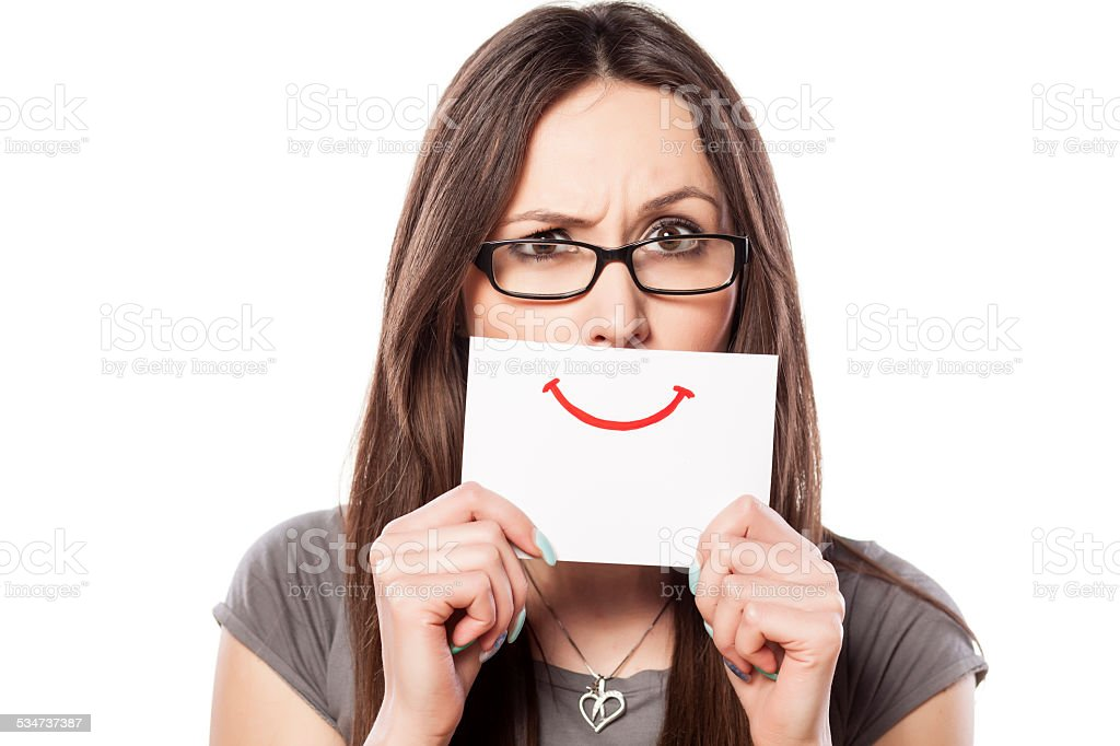 Angry young woman with smile painted on paper stock photo