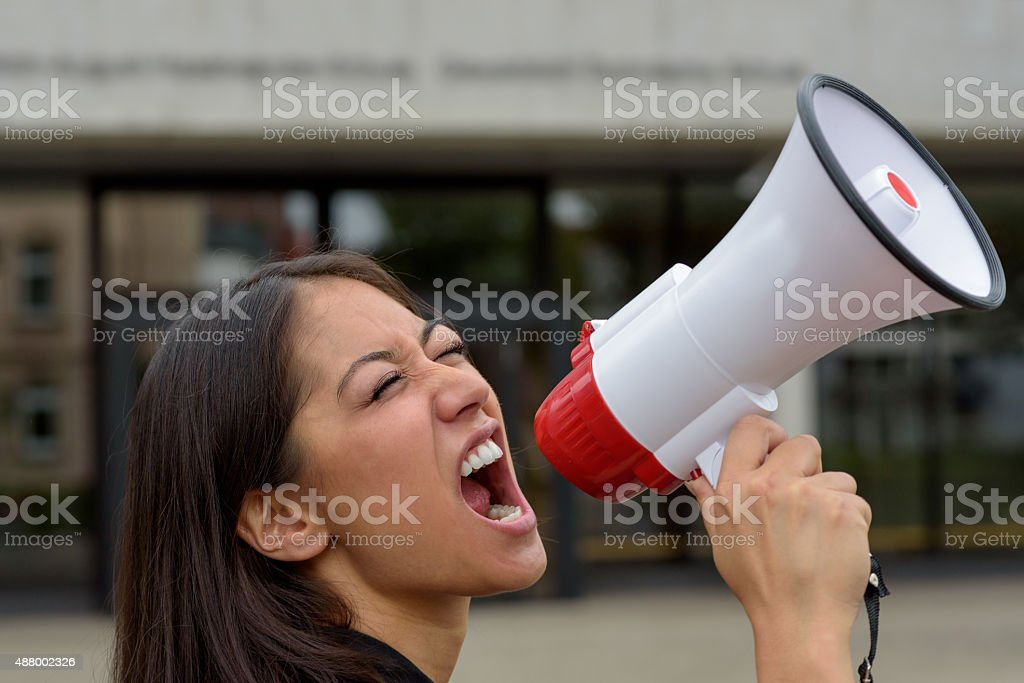 Angry young woman yelling over a megaphone stock photo