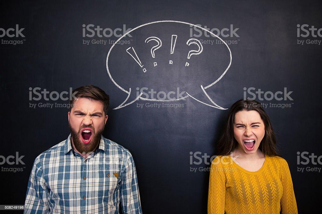 Angry youple shouting over blackboard background stock photo