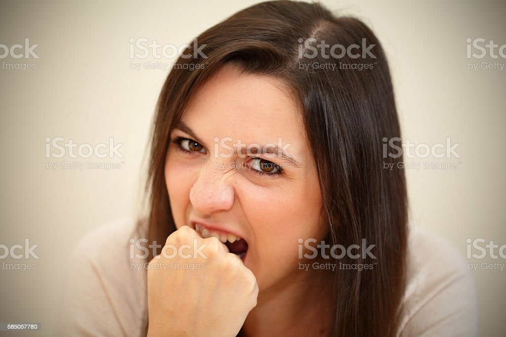 angry,frustrated women biting her hand concept stock photo
