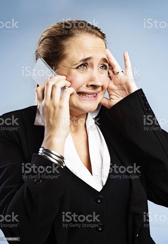 Anguished businesswoman gets bad news on mobile phone stock photo