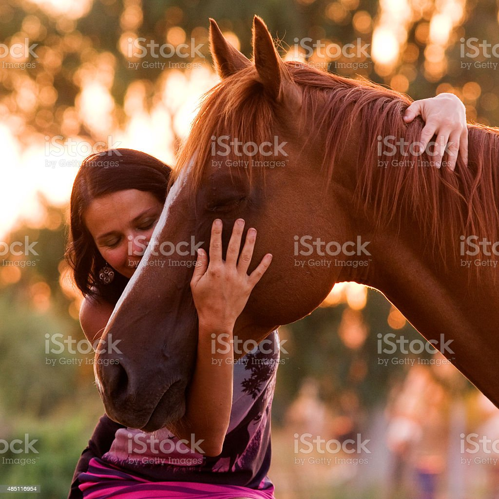 Pretty women is hugging and kissing her handsome horse shortly before...