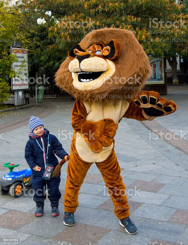 Animator in a lion costume entertaining children stock photo