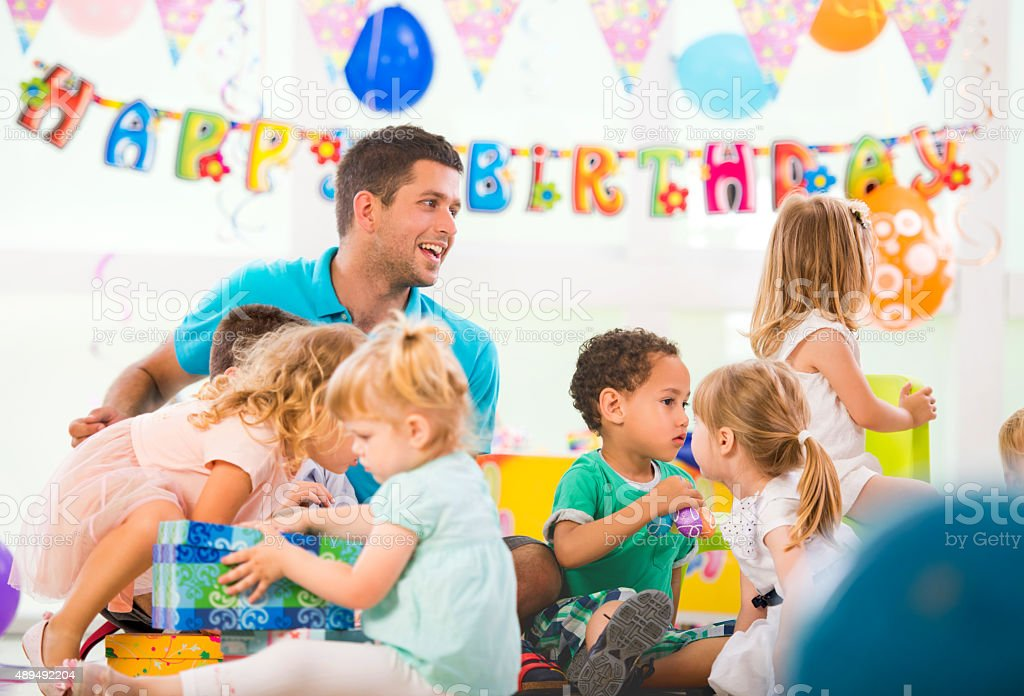 Animator playing entertaining happy children at birthday party. stock photo