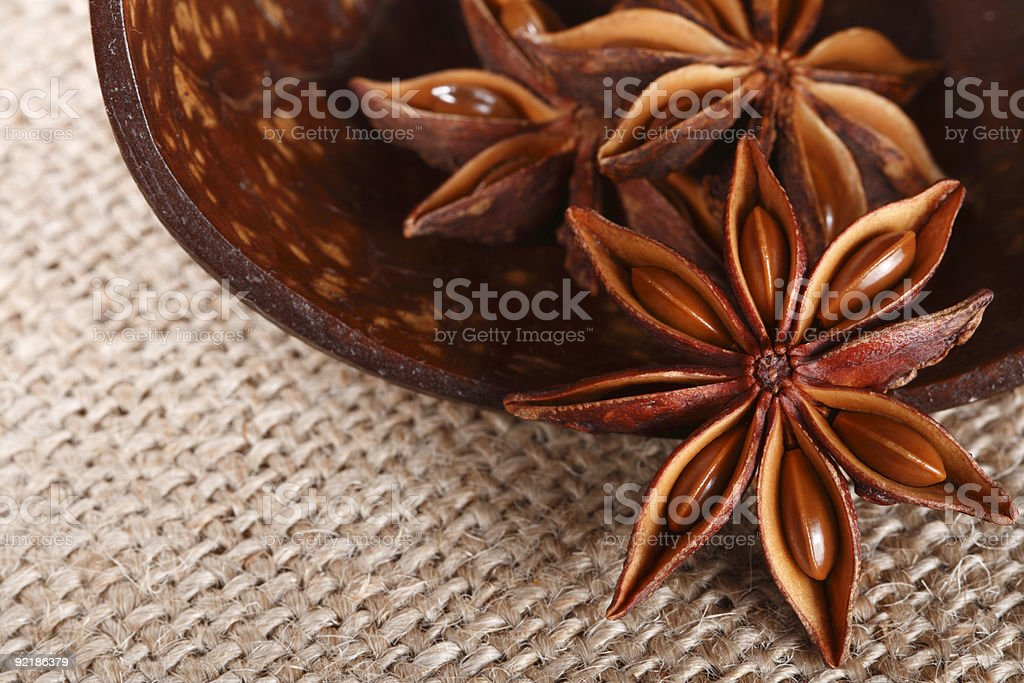 anis star in a wooden cup on burlap background, close-up royalty-free stock photo