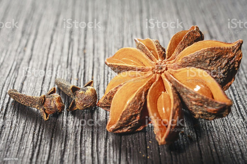 Anise stars and cloves on wooden background stock photo