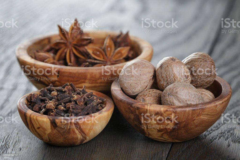 anise stars, cloves and nutmeg on oak table stock photo