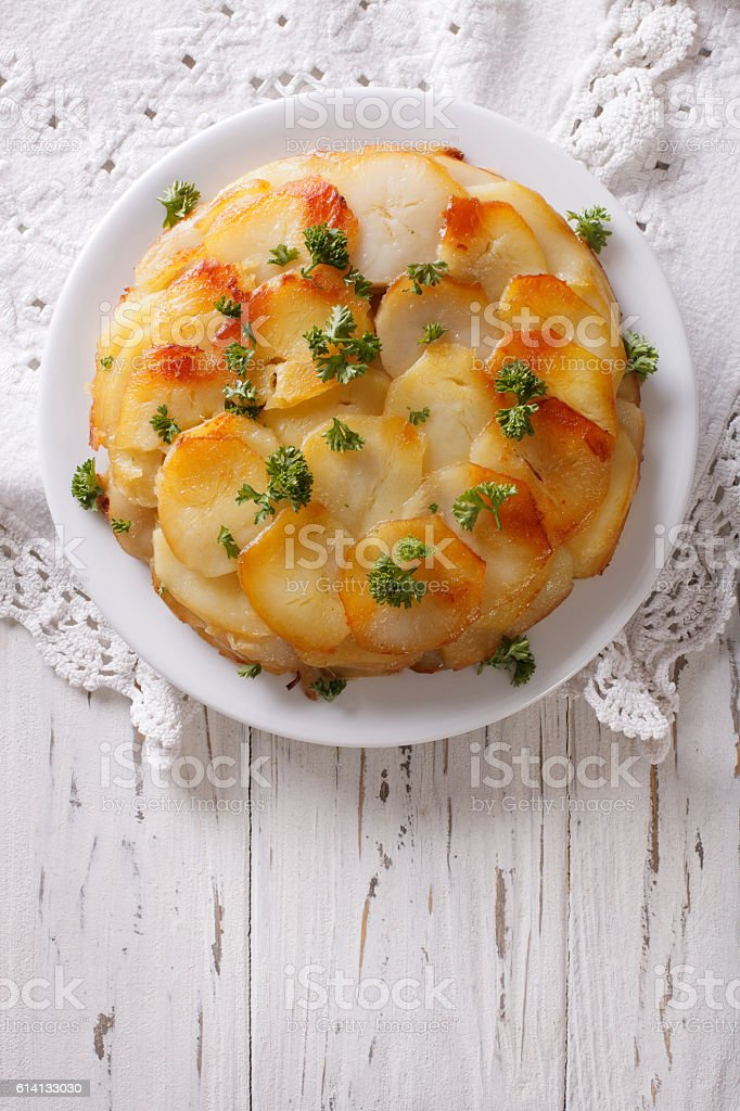 Anna potatoes with butter on a plate. Vertical  top view stock photo