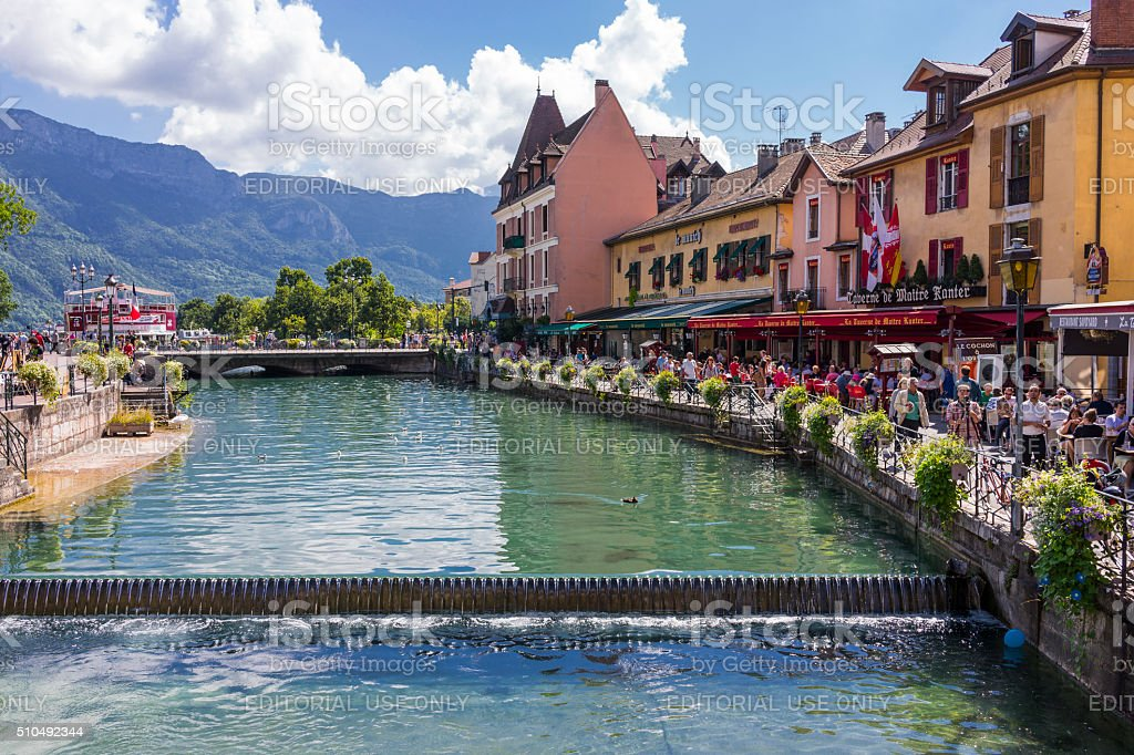 Annecy, France. Building facades on a canal with tourists stock photo