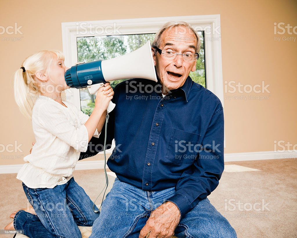 Announcement Little Girl Talking to Deaf Grandpa stock photo