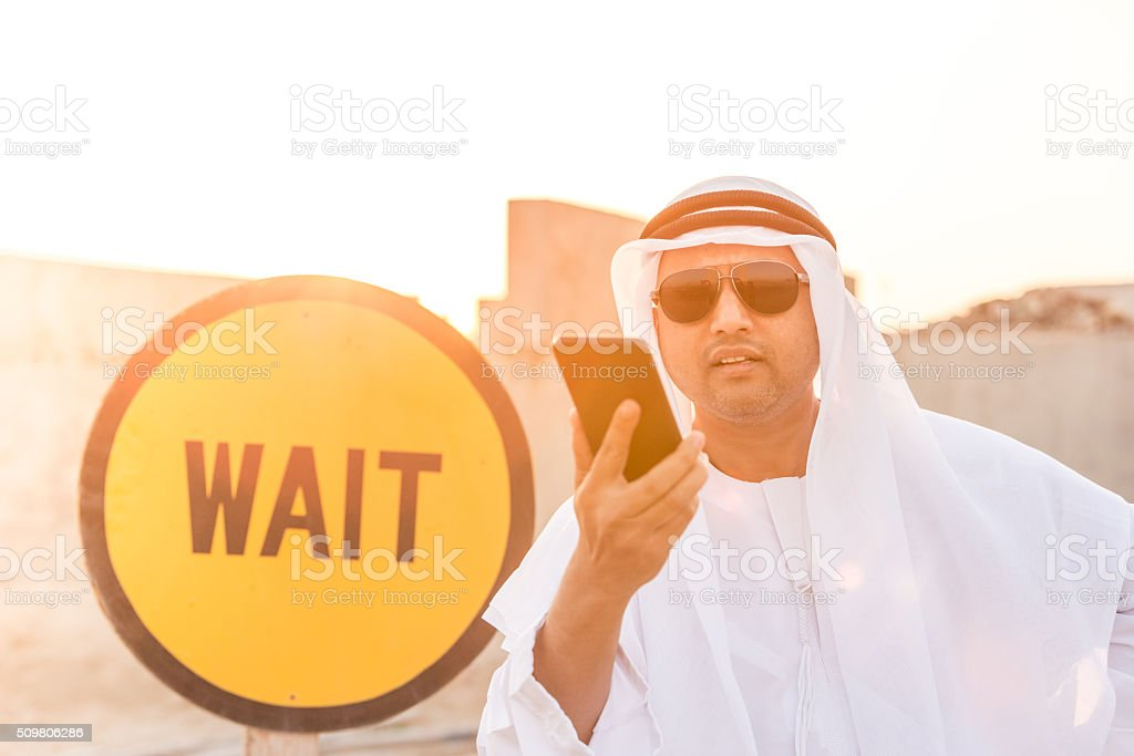 Annoyed Arab Near the Wait Sign at a Construction Site stock photo