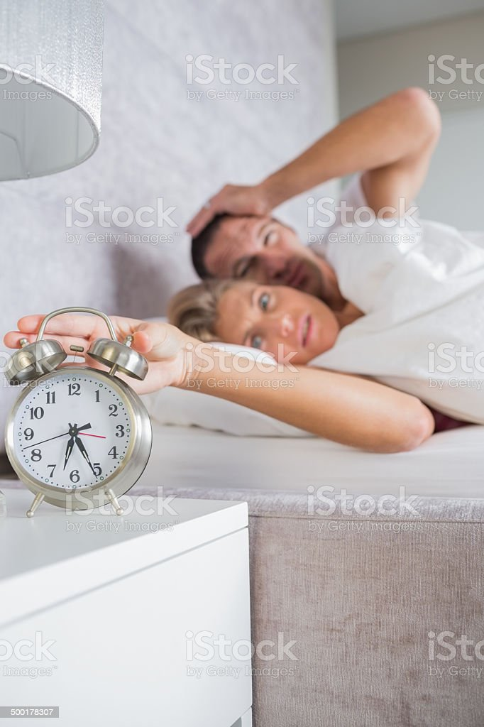 Annoyed couple looking at alarm clock in the morning stock photo