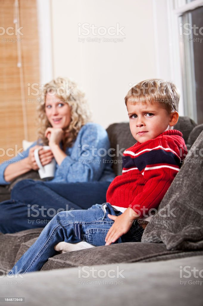 Annoyed little boy, mother smiling in background stock photo