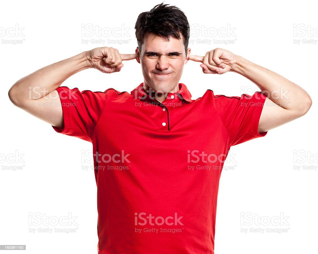 Annoyed Man With Fingers Plugging Ears stock photo