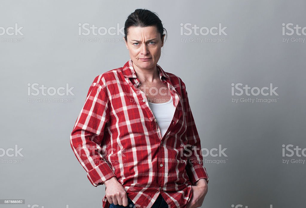 annoyed mature woman standing showing her doubt and disagreement stock photo
