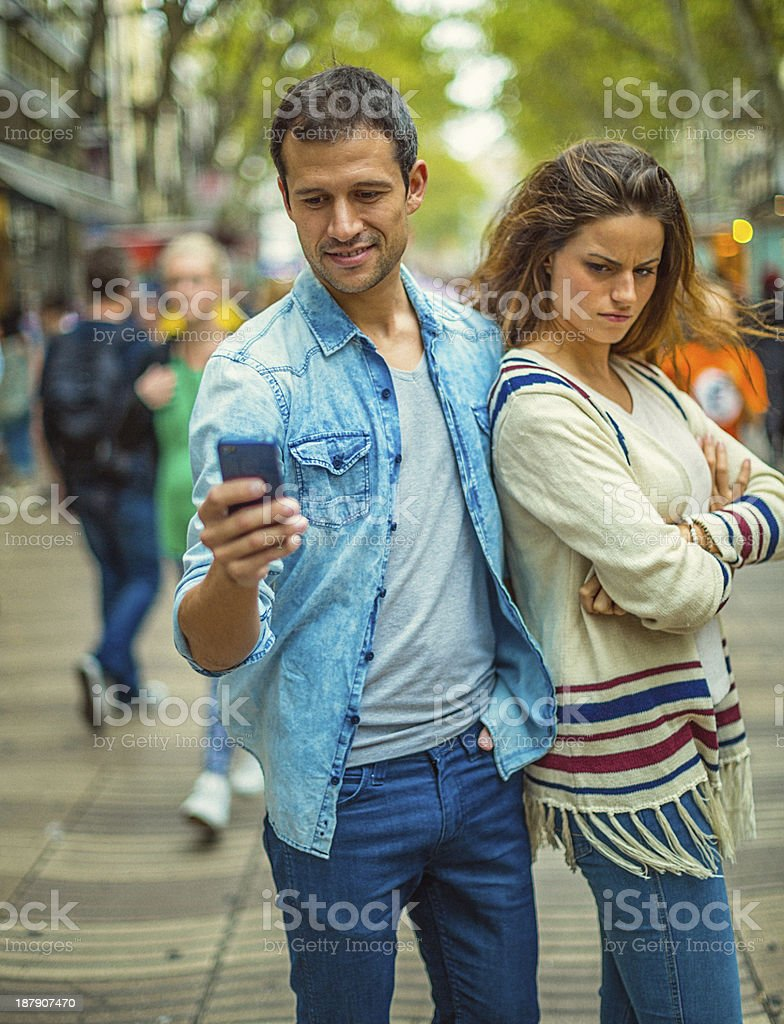 Annoyed woman at texting boyfriend royalty-free stock photo