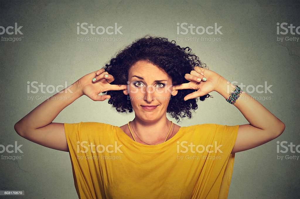 Annoyed woman plugging ears with fingers doesn't want to listen stock photo