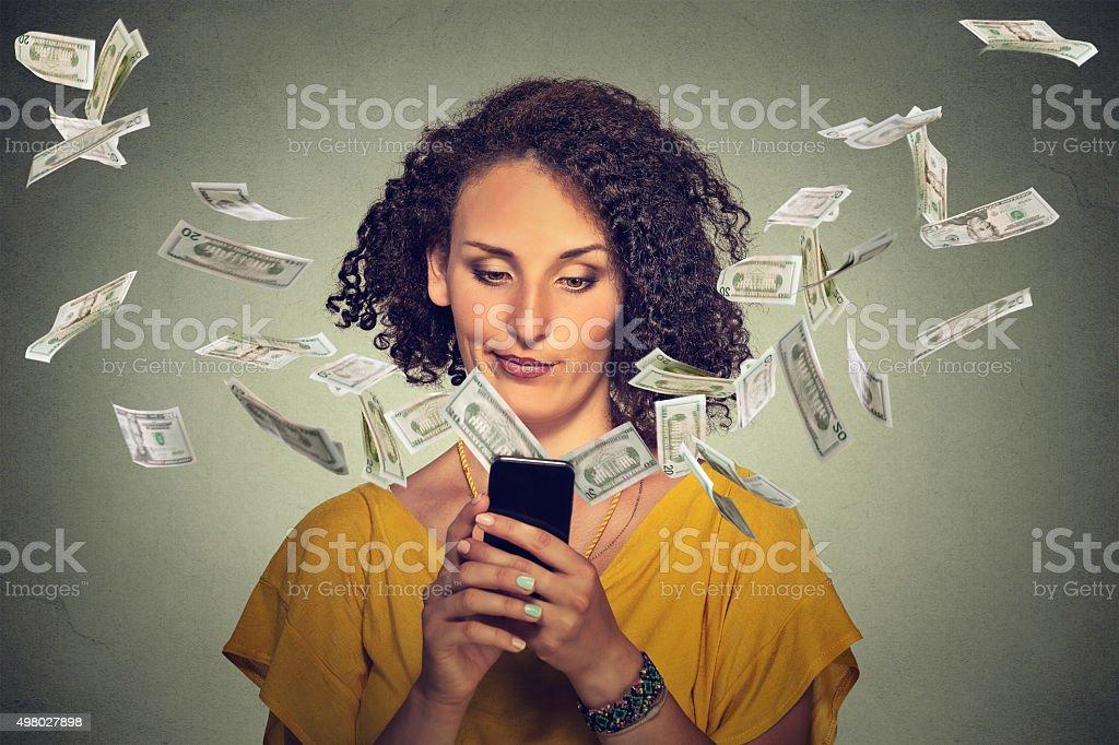 Annoyed woman using smartphone dollar bills flying away stock photo
