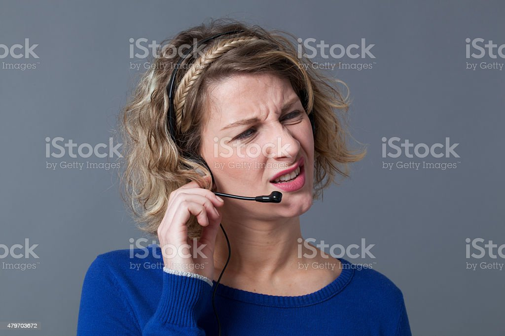 annoyed young female professional working for a call center stock photo