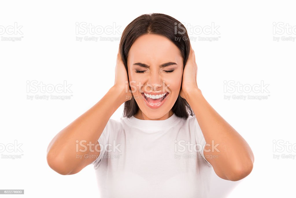 annoyed young woman plugging ears with hands stock photo