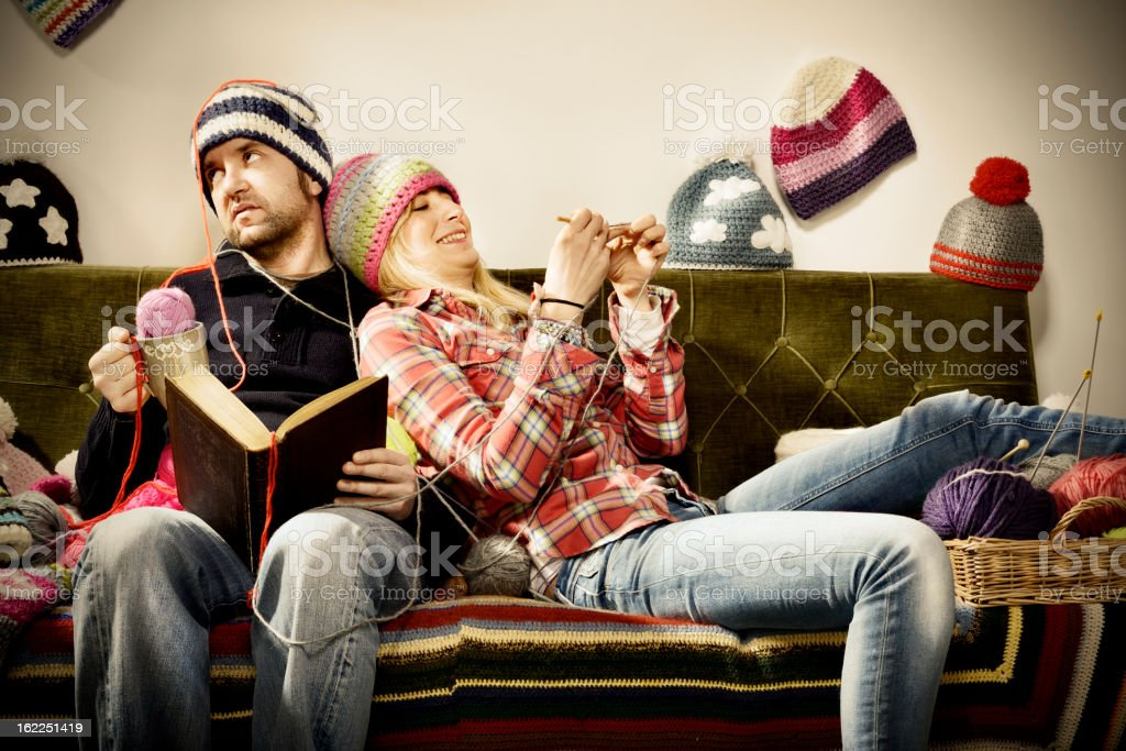 Annoying young knitter woman couple portrait on couch stock photo