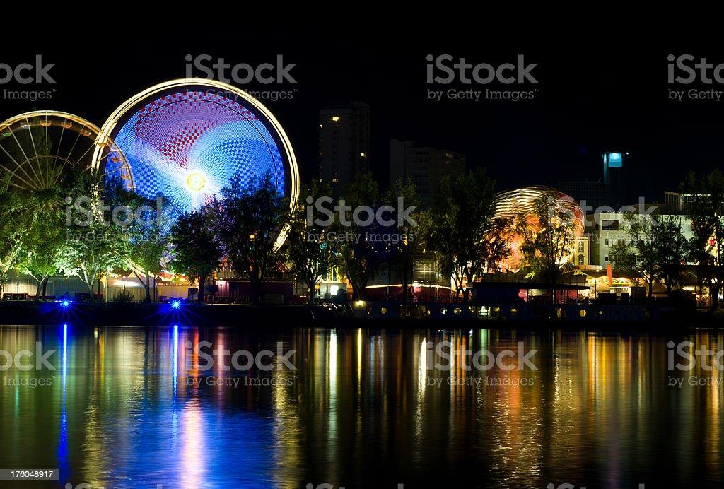annual fair amusement park beside a river at night stock photo