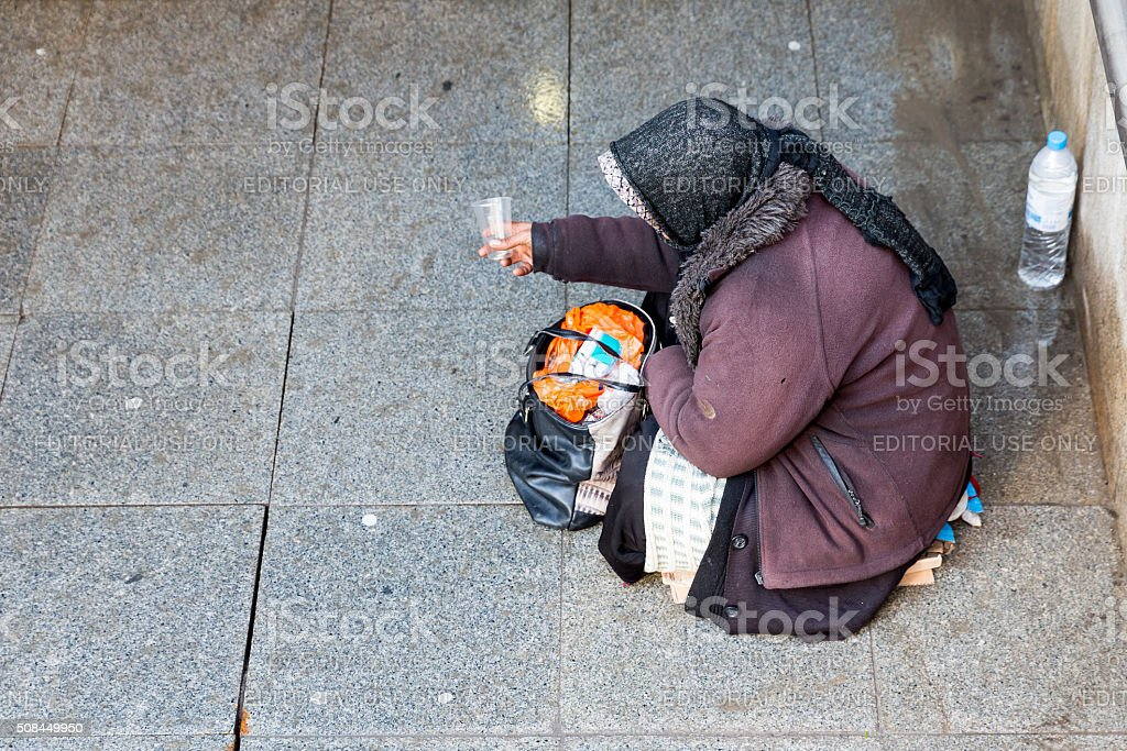 Anonymous female beggar stock photo